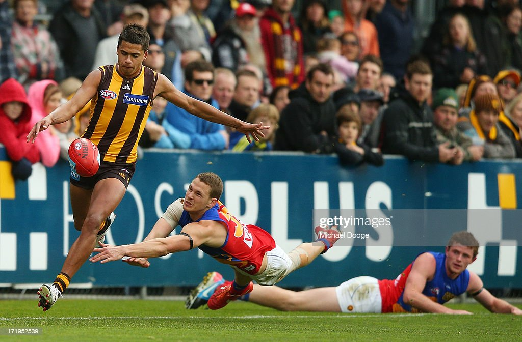 Bradley Hill of the Hawks kicks the ball away from Jack Redden (C) and Pearce Hanley of the Lions during the round 14 AFL match between the Hawthorn Hawks and the Brisbane Lions at Aurora Stadium on June 30, 2013 in Launceston, Australia.