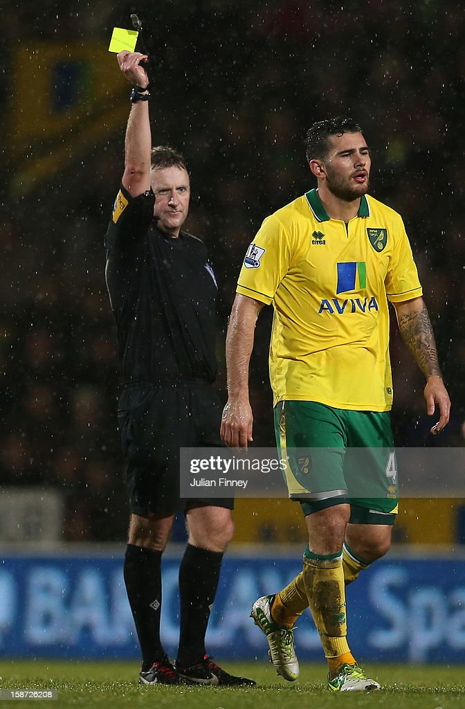 Bradley Johnson of Norwich City receives a yellow card from referee Jonathan Moss during the Barclays Premier League match between Norwich City and Chelsea at Carrow Road on December 26, 2012 in Norwich, England.