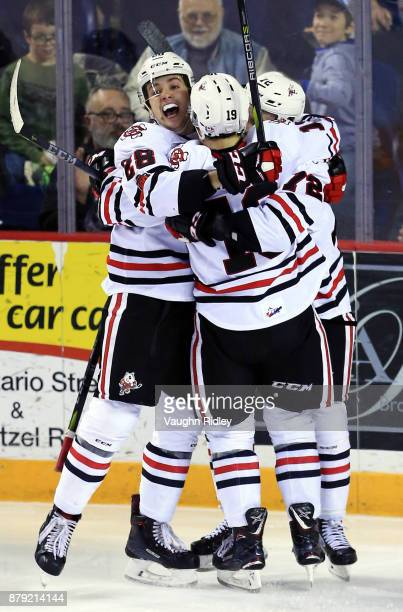 Bradley Johnson of the Niagara IceDogs celebrates a goal with Andrew Bruder and Ian Martin during the second period of an OHL game against the...