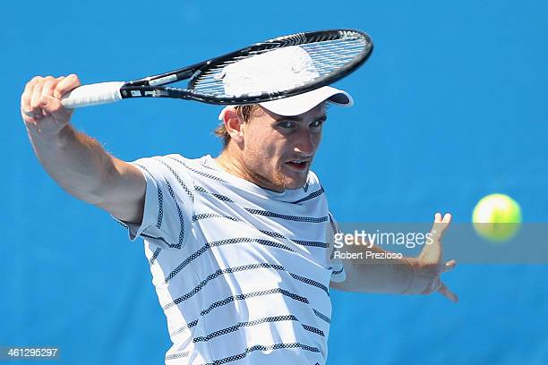 Bradley Mousley of Australia plays a backhand in his match against Vincent Millot of France during qualifying for the 2014 Australian Open at...