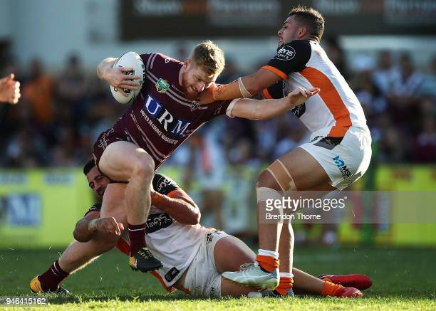 Bradley Parker of the Sea Eagles is tackled by the Tigers defence during the round six NRL match between the Manly Sea Eagles and the Wests Tigers at...