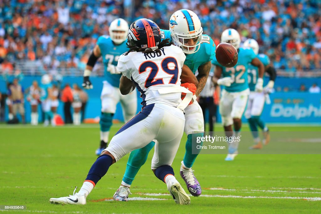 Bradley Roby #29 of the Denver Broncos forces a fumble during the third quarter against the Miami Dolphins at the Hard Rock Stadium on December 3, 2017 in Miami Gardens, Florida.