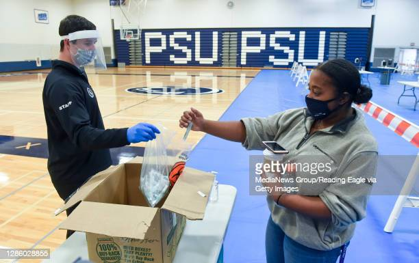 Bradley Strauss, the testing site manager holds open a bag for a Penn State Berks Student to put her test in. At the Penn State Berks Beaver...