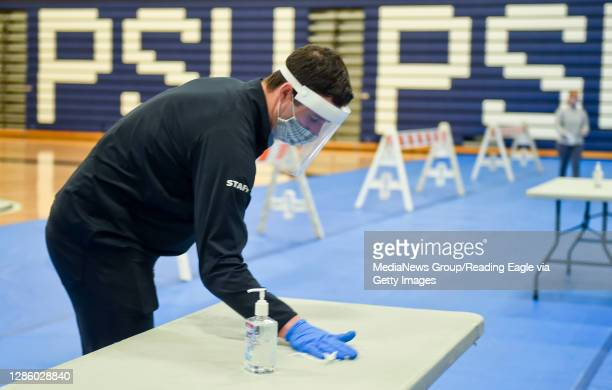 Bradley Strauss, the testing site manager wipes down a table between students doing tests. At the Penn State Berks Beaver Community Center gymnasium...