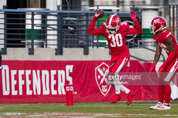 Bradley Sylve of the DC Defenders celebrates with teammates after returning an interception for a touchdown against the Seattle Dragons during the...