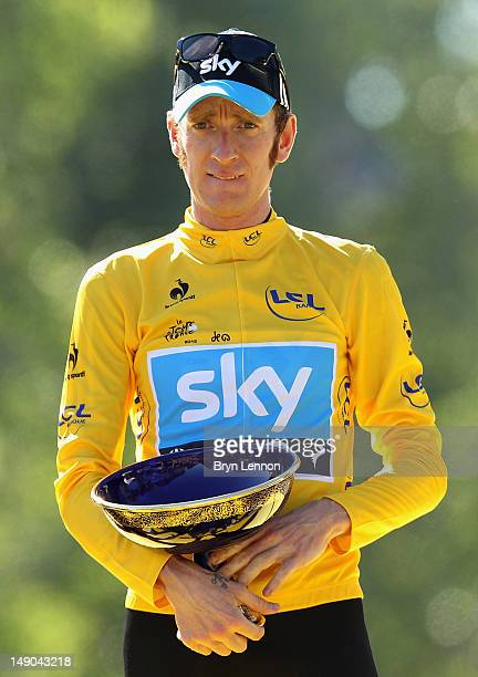 Bradley Wiggins of Great Britain and SKY Procycling celebrates after receiving the maillot jaune on the podium and winning the general...