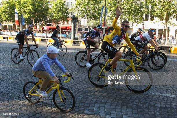 Bradley Wiggins of Great Britain and SKY Procycling celebrates with his son and teammates on a processional lap after winning the 2012 Tour de France...