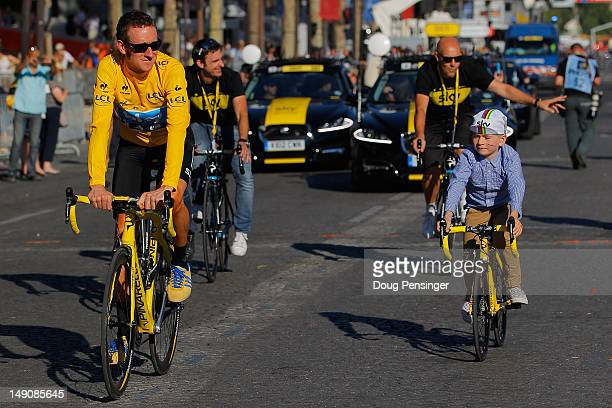 Bradley Wiggins of Great Britain and SKY Procycling celebrates with his son on a processional lap after winning the 2012 Tour de France after the...