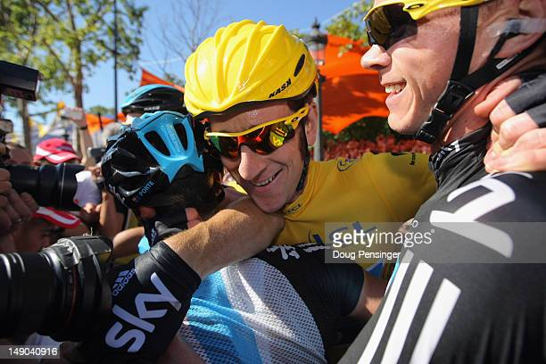 Bradley Wiggins of Great Britain and SKY Procycling hugs teammates after winning the general classification during the twentieth and final stage of...