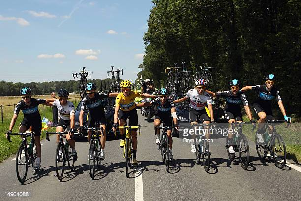 Bradley Wiggins of Great Britain and SKY Procycling poses with teammates as he celebrates riding to Paris in the maillot jaune securing the yellow...