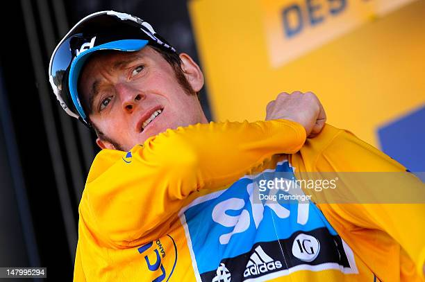 Bradley Wiggins of Great Britain riding for Sky Procycling takes the podium after he earned the race leader's yellow jersey in stage seven of the...