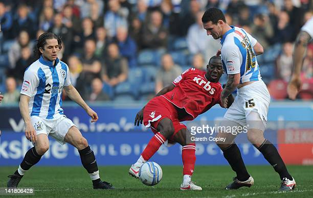 Bradley WrightPhillips of Charlton is tackled by Joey Gudjonsson and Sean Morrison of Huddersfield during the npower League One match between...