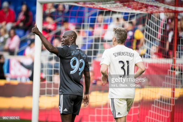 Bradley WrightPhillips of New York Red Bulls holds up a thumbs up to teammate while being covered by Bastian Schweinsteiger of Chicago Fire during...