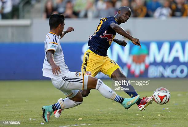 Bradley WrightPhillips of New York Red Bulls shoots the ball while defended by AJ DeLaGarza of Los Angeles Galaxy in the first half at StubHub Center...