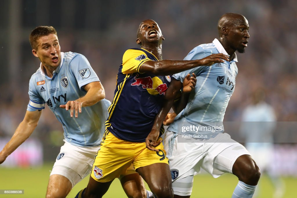 Bradley Wright-Phillips #99 of the New York Red Bulls is hit by Matt Besler #5 and Ike Opara #3 of Sporting Kansas City in the US Open Cup Final match at Children's Mercy Park on September 20, 2017 in Kansas City, Kansas.