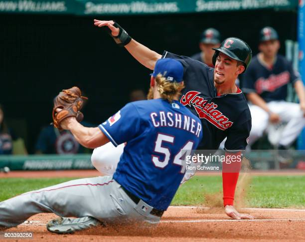 Bradley Zimmer of the Cleveland Indians scores on a wild pitch against pitcher Andrew Cashner of the Texas Rangers during the third inning at...