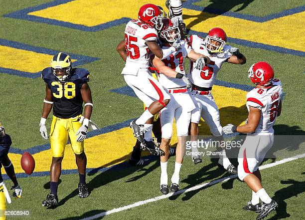 Bradon Godfrey of the Utah Utes celebrates a second quarter touchdown with Brent Casteel, Jereme Brooks and Derrell Mack in front of Artis Chambers...