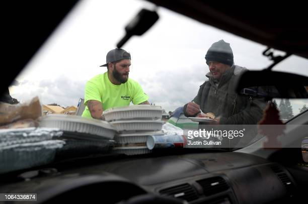 Bradway Burdine serves Camp Fire evacuees a Thanksgiving meal at a makeshift evacuation camp next to a Walmart store on November 22 2018 in Chico...