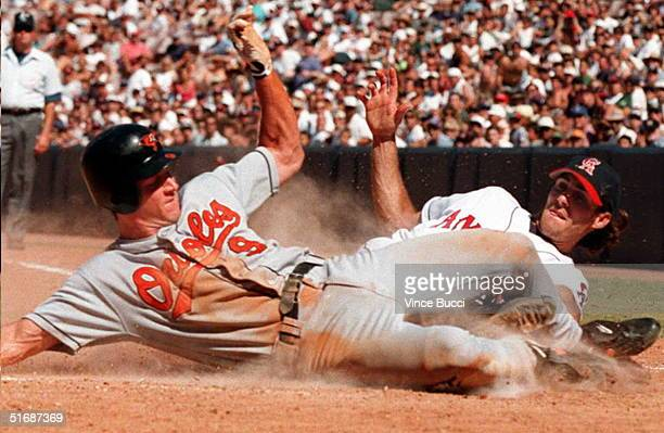 Brady Anderson of the Baltimore Orioles slides safely across home plate ahead of throw to pitcher Mike James of the California Angels on a wild pitch...