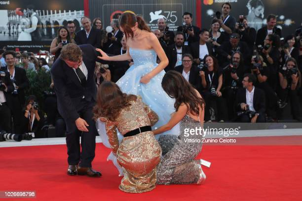 Brady Corbet Natalie Portman Stacy Martin help Raffey Cassidy with her shoes on the red carpet ahead of the 'Vox Lux' screening during the 75th...