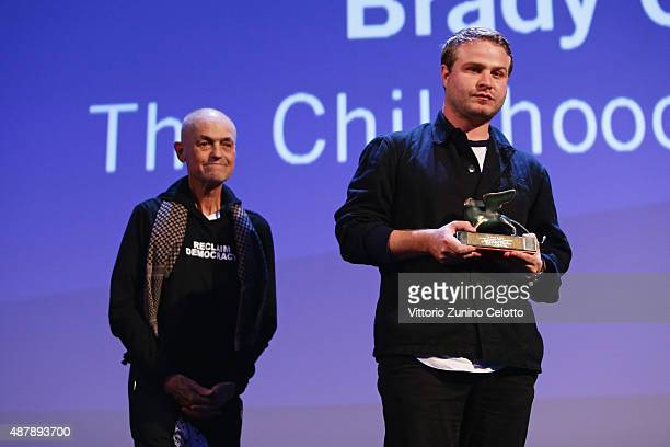 Brady Corbet with the Orizzonti Award for Best Director for 'The Childhood of a Leader' with jury president Jonathan Demme on stage at the closing...
