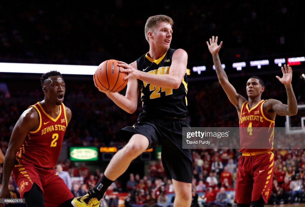 Brady Ellingson #24 of the Iowa Hawkeyes passes the ball as Cameron Lard #2 of the Iowa State Cyclones, and Donovan Jackson #4 of the Iowa State Cyclones defend in the second half of play at Hilton Coliseum on December 7, 2017 in Ames, Iowa. The Iowa State Cyclones won 84-78 over the Iowa Hawkeyes.