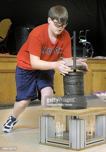 Brady Grotton from Jefferson Village School lowers weights down onto two balsa wood columns as his teammates perform a skit in the Column Structure...