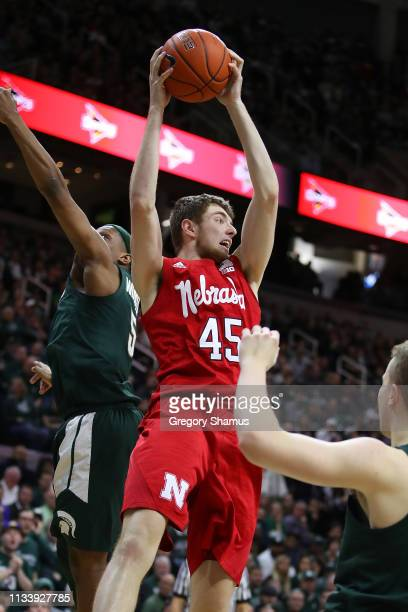 Brady Heiman of the Nebraska Cornhuskers grabs a rebound in front of Cassius Winston of the Michigan State Spartans during the second half at Breslin...