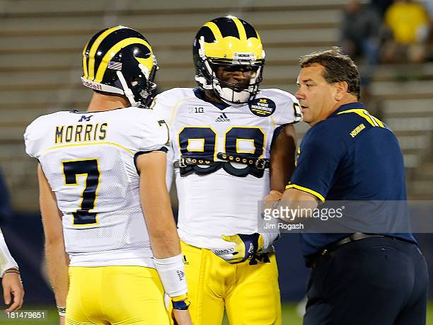 Brady Hoke coach of the Michigan Wolverines talks with Devin Gardner and Shane Morris before a game with the Connecticut Huskies at Rentschler Field...