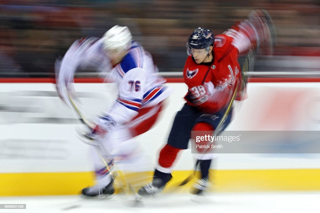 Brady Skjei #76 of the New York Rangers and Alex Chiasson #39 of the Washington Capitals battle for the puck during the second period at Capital One Arena on December 08, 2017 in Washington, DC.