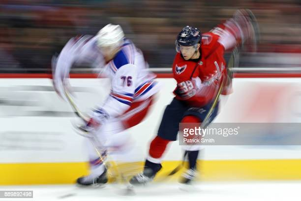 Brady Skjei of the New York Rangers and Alex Chiasson of the Washington Capitals battle for the puck during the second period at Capital One Arena on...