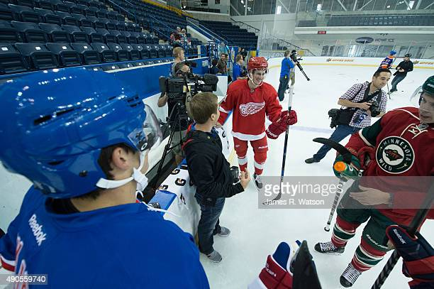 Brady Skjei of the New York Rangers Dylan Larkin of the Detroit Red Wings and Mike Reilly of the Minnesota Wild receive instructions ahead of a photo...