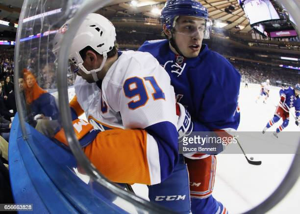 Brady Skjei of the New York Rangers hits John Tavares of the New York Islanders into the boards at Madison Square Garden on March 22 2017 in New York...