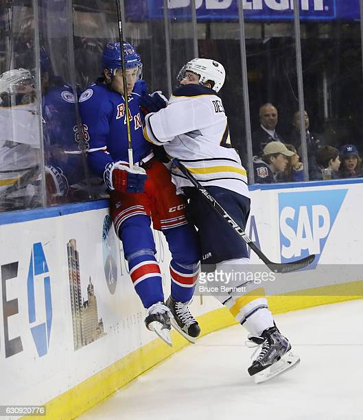 Brady Skjei of the New York Rangers is checked into the boards by Nicolas Deslauriers of the Buffalo Sabres during the third period at Madison Square...