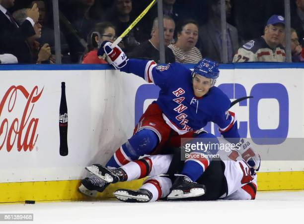 Brady Skjei of the New York Rangers lands on top of Nico Hischier of the New Jersey Devils during the first period at Madison Square Garden on...