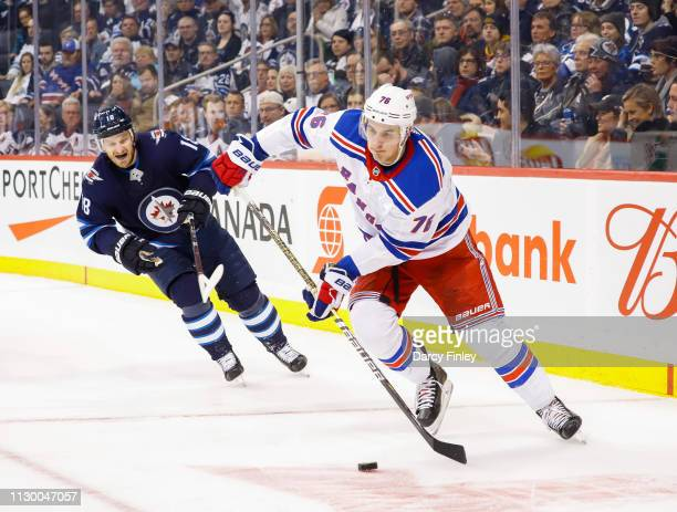 Brady Skjei of the New York Rangers plays the puck up the ice as Bryan Little of the Winnipeg Jets gives chase during third period action at the Bell...