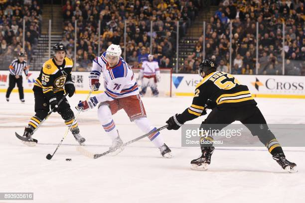 Brady Skjei of the New York Rangers skates with the puck against Noel Acciari and Sean Kurlay of the Boston Bruins at the TD Garden on December 16...