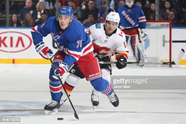 Brady Skjei of the New York Rangers skates with the puck against Johnny Gaudreau of the Calgary Flames at Madison Square Garden on February 9 2018 in...