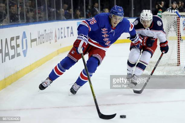 Brady Skjei of the New York Rangers skates with the puck against Artemi Panarin of the Columbus Blue Jackets in the first period during their game at...