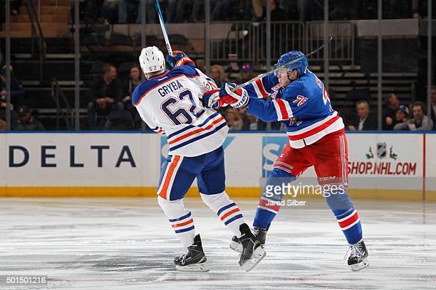 Brady Skjei of the New York Rangers throws a hit against Eric Gryba of the Edmonton Oilers at Madison Square Garden on December 15 2015 in New York...