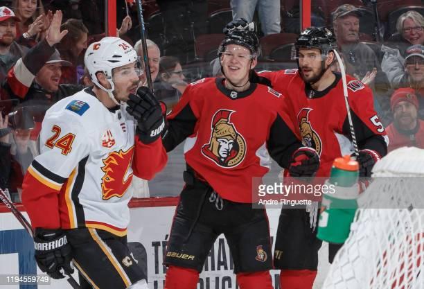 Brady Tkachuk of the Ottawa Senators celebrates his first period goal with teammate Artem Anisimov as Travis Hamonic of the Calgary Flames looks on...