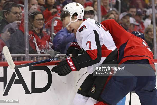 Brady Tkachuk of the Ottawa Senators is checked by Matt Niskanen of the Washington Capitals during the first period at Capital One Arena on February...