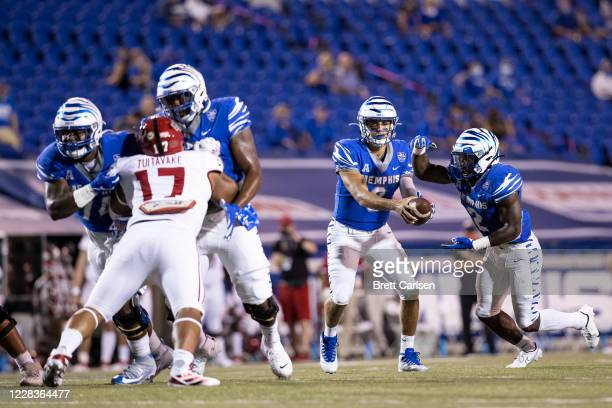 Brady White hands the ball to Rodrigues Clark of the Memphis Tigers for a touchdown carry to tie the game at 14-14 during the second quarter against...