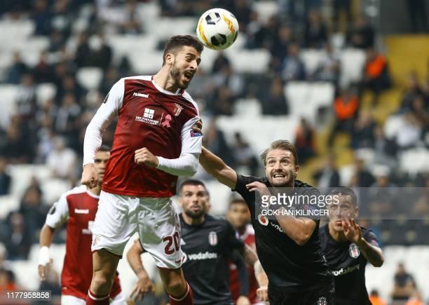 Braga's Portuguese forward Paulinho jumps for the ball next to Besiktas' Turkish defender Caner Erkin during the UEFA Europa League Group K football...