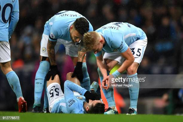 Brahim Diaz of Manchester City goes down injured consoled by Alexander Zinchenko of Manchester City and Nicolas Otamendi of Manchester City during...