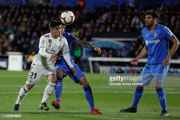 Brahim Diaz of Real Madrid CF competes for the ball with Mauro Arambarri of Getafe CF during the La Liga match between Getafe CF and Real Madrid CF...