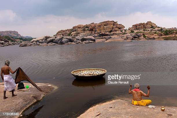 Brahmin doing a puja on the bank of the Tunggabhadra river in Hampi while a sadhu is doing his laundry.