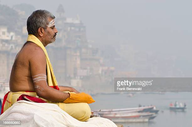 Brahmin meditating at the holy river Ganges in the morning..