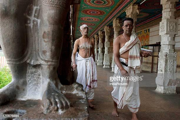 Brahmin priests walking through the pillared corridors inside the Madurai Meenakshi Temple complex Madurai Tamil Nadu India