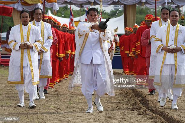 Brahmin sprinkles holy water during the the annual Royal Ploughing Ceremony to mark the traditional beginning of the ricegrowing season at Sanam...